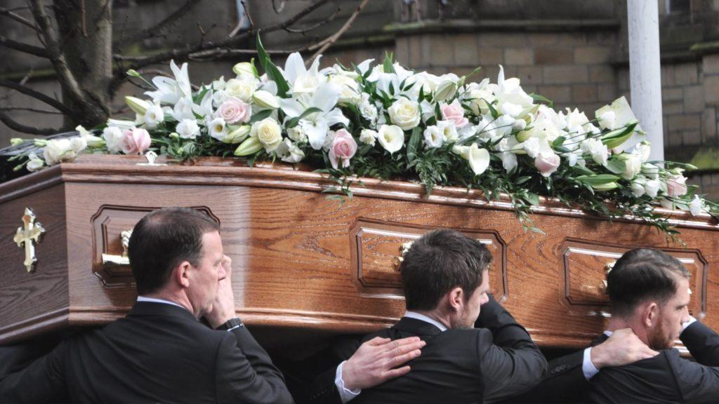 Coffin being lifted by gentlemen